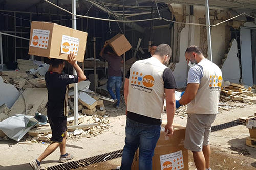 Boxes of personal protective equipment are carried over rubble. © UNFPA Lebanon