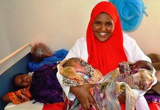 A midwife welcomes twins after a safe delivery at a UNFPA-supported health center in Somalia.