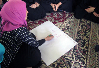 "A displaced woman writes down her dreams as part of the ""Our Dreams"" group support session"