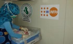 إحدى العاملات فى مجال الصحة تقوم بالكشف الدوري على طفل حديث الولادة فى غرفة الولادة  التابع لصندوق الأمم المتحدة للسكان في مخيم الحبانية، بمحافظة الأنبار، وسط العراق.