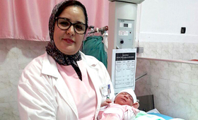 Khadija Bahzad holds a baby she delivered in Marrakech. Ms. Bahzad is a midwifery trainer, strengthening the skills of other midwives in the country. © UNFPA