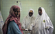 Two midwives place an intravenous drip for a patient at the maternity ward of Banadir Hospital in Mogadishu.